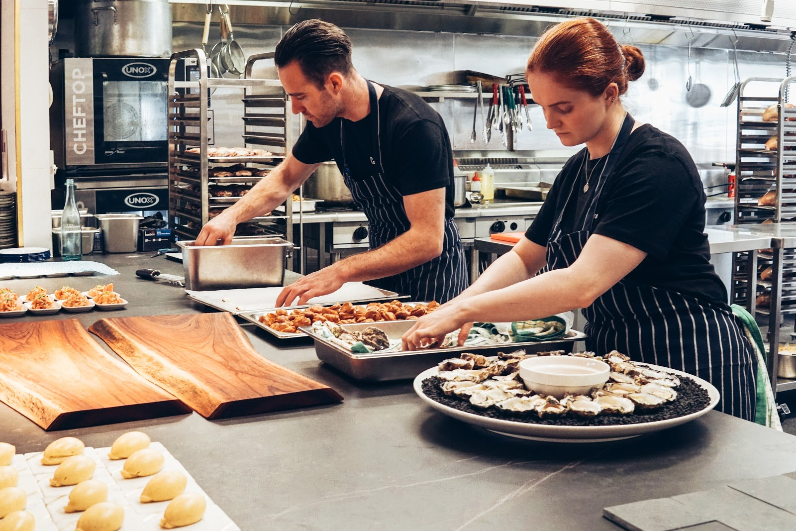 Used restaurant equipment: Two cooks in striped aprons preparing food