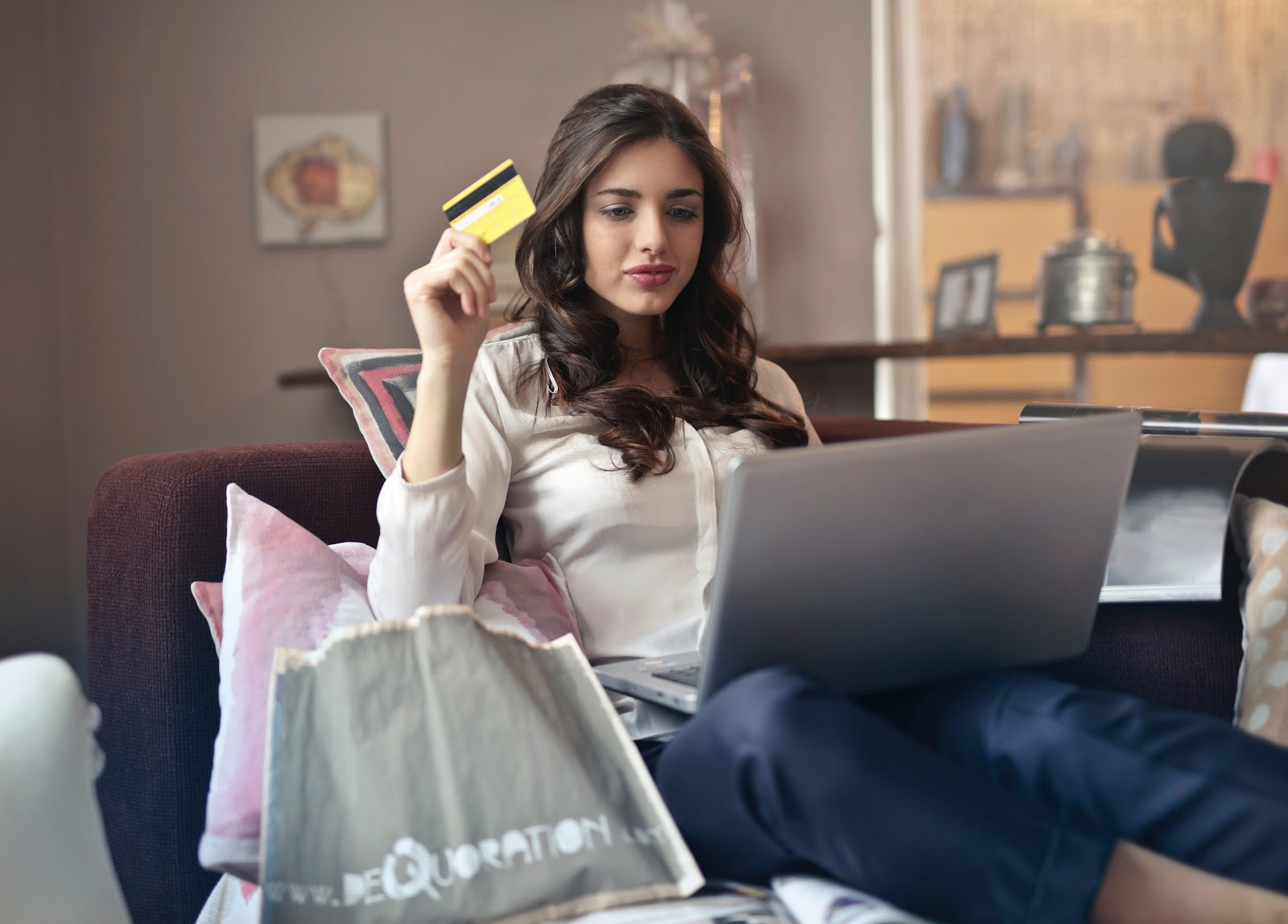 Woman holding credit card while using laptop