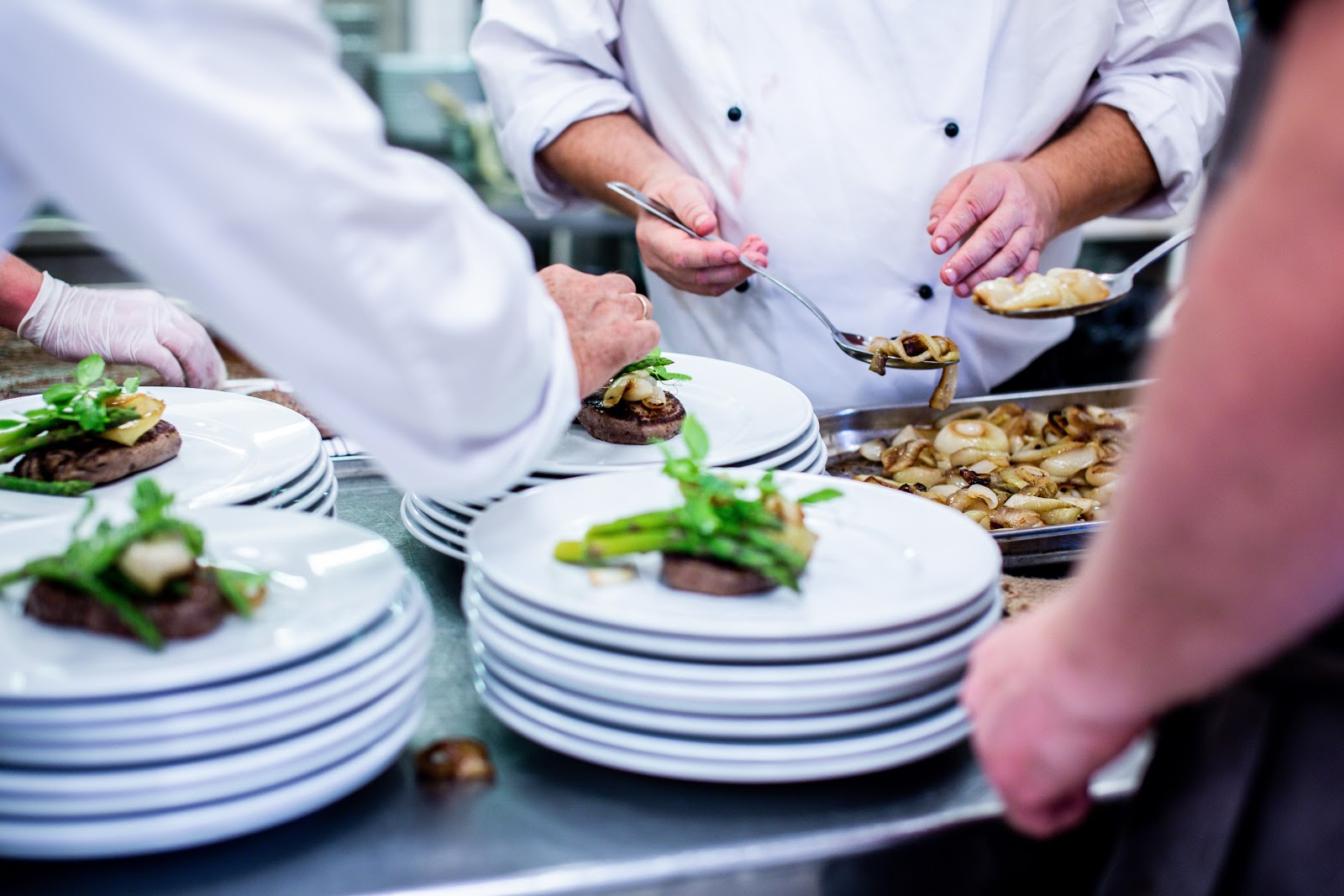 Chefs add food to white plates