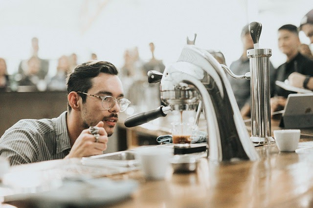 Employee watches as espresso pours into shot glass