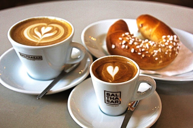 Two coffee drinks with latte art and a pastry