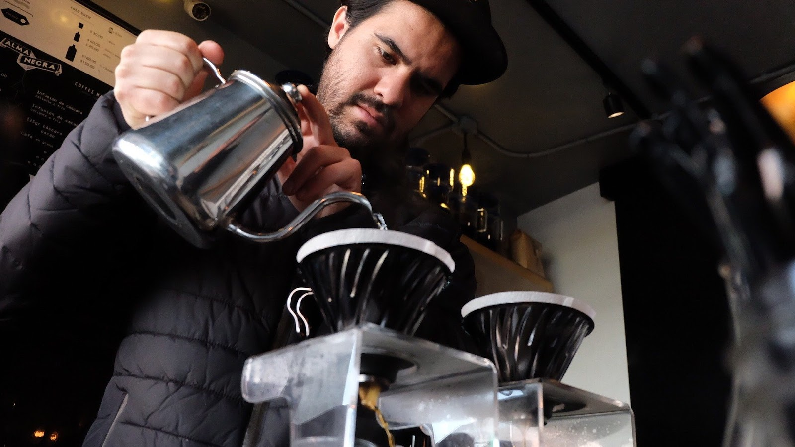 Barista job description: Man pours water into pourover cup