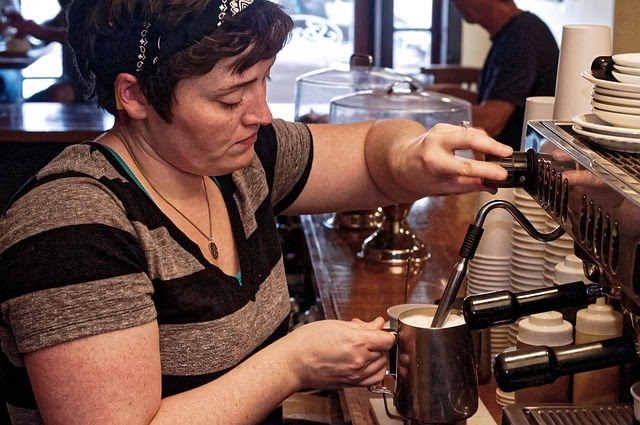 Barista job description: Woman steams milk