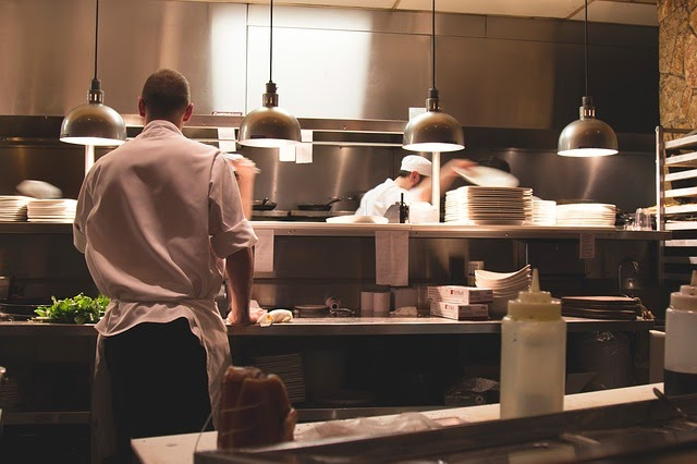 Chef standing at the window in a restaurant kitchen