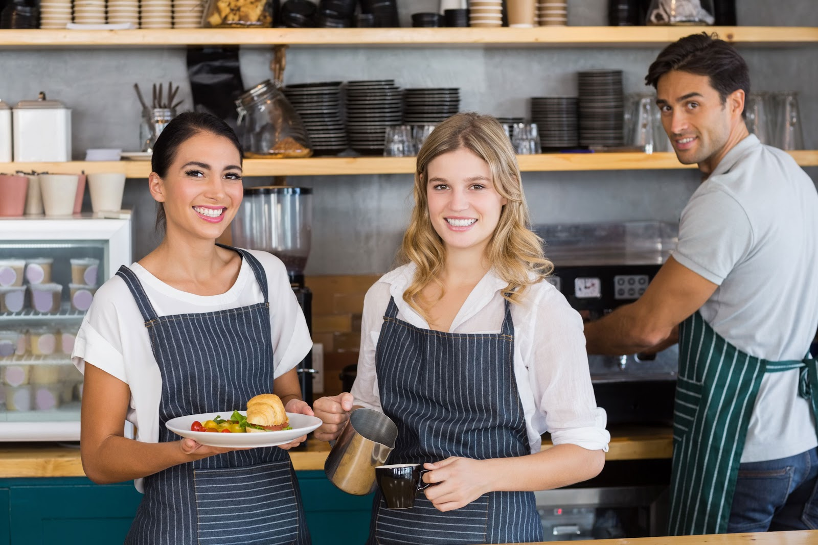 Three servers working behind the counter and smiling at camera