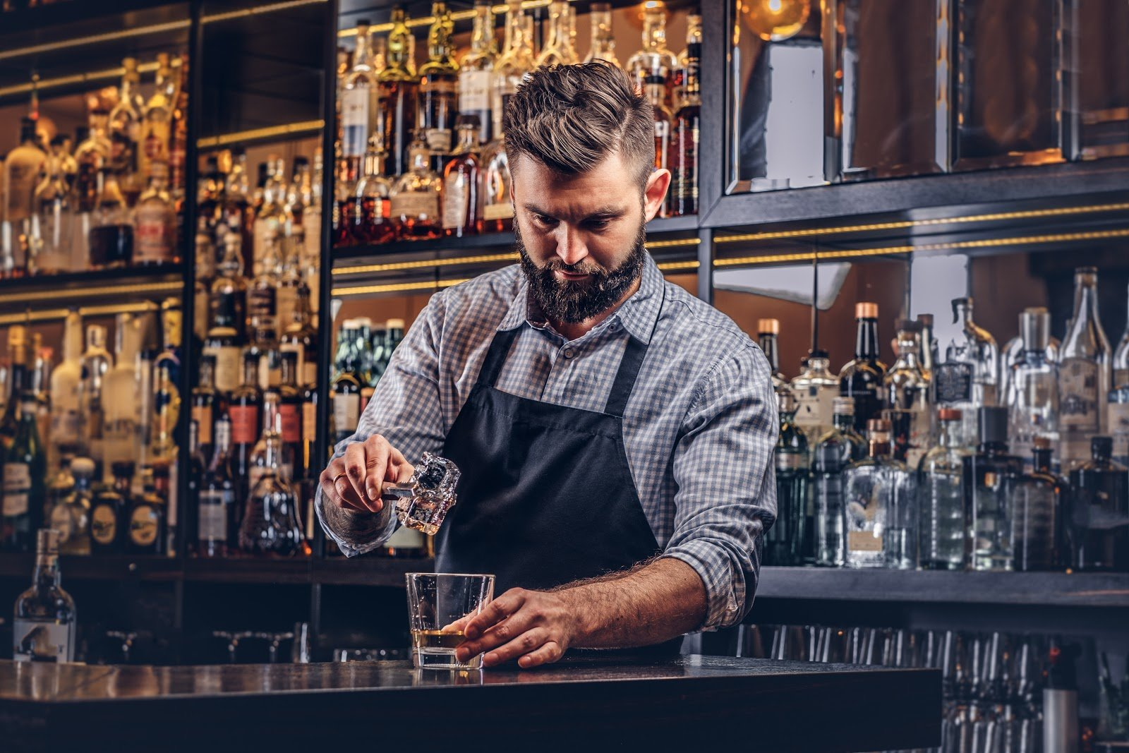 Bartender pours shot into glass