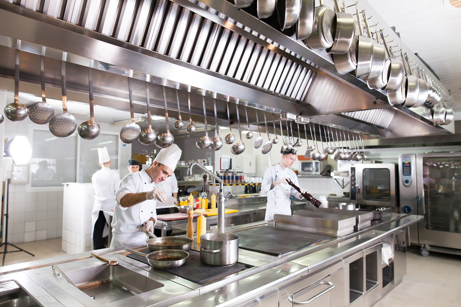 Chefs work at stations in kitchen