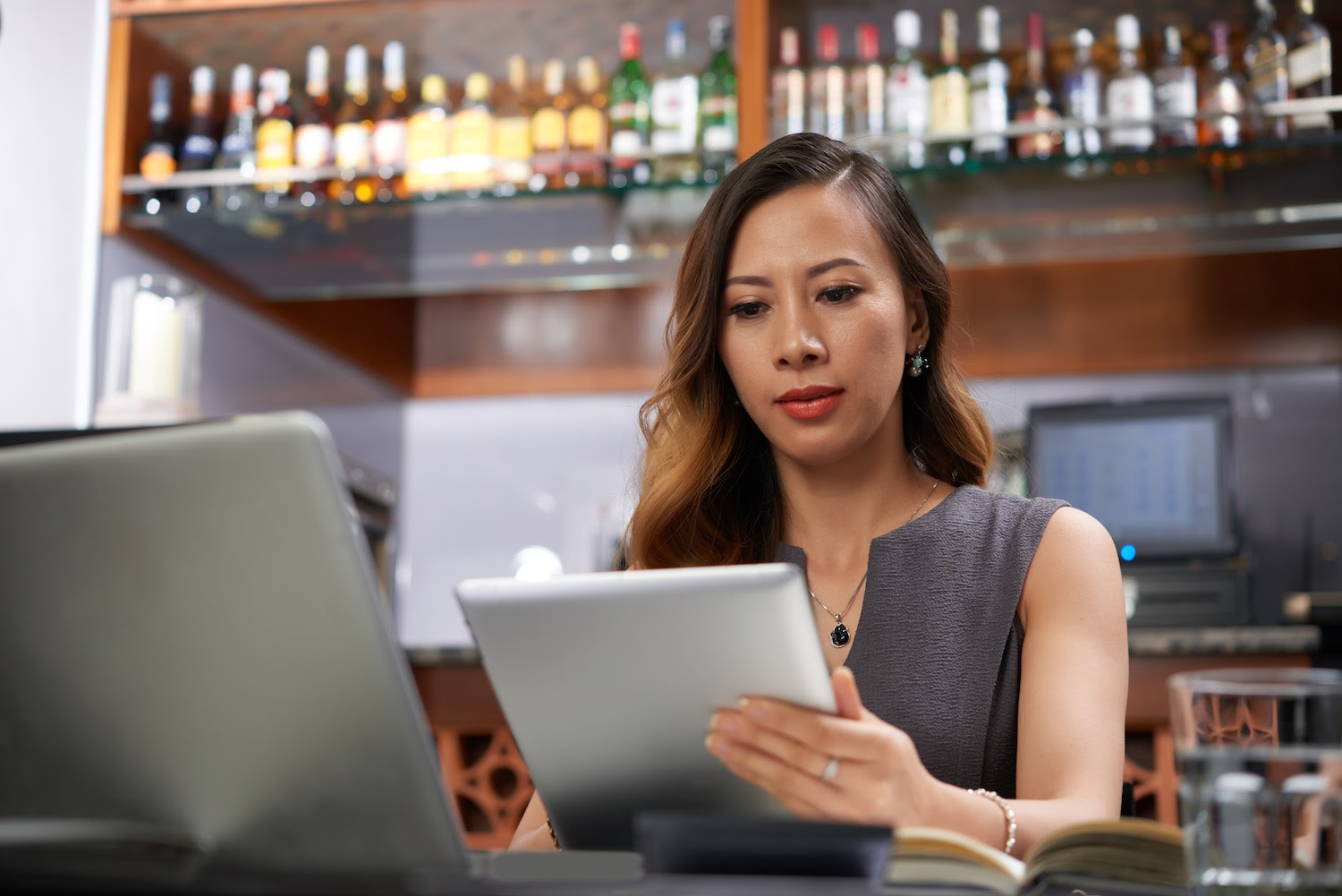 Bartender looks at iPad with laptop open in front of her