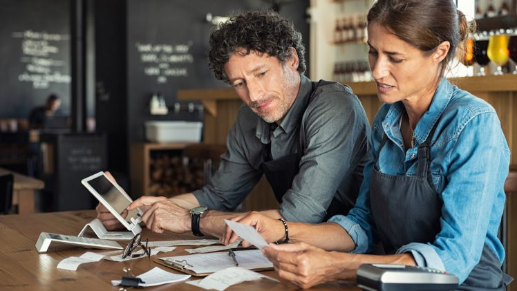 Restaurant accounting: Man and woman look over receipts while on shift