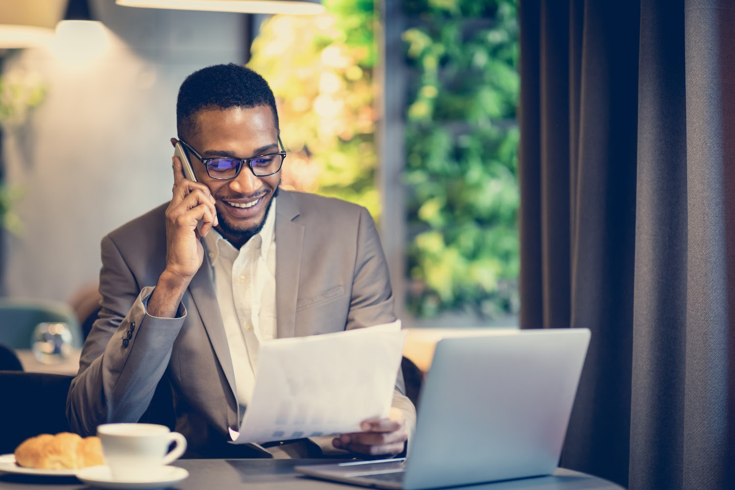 Restaurant accounting: Man talks on phone, smiling, while holding a piece of paper