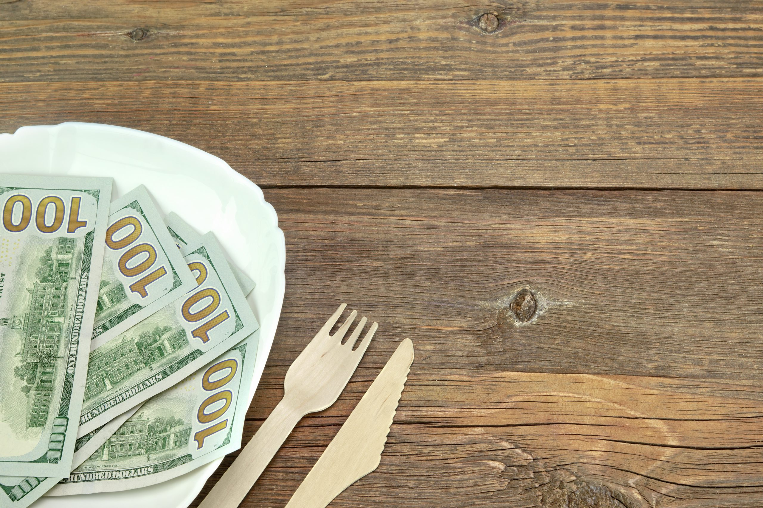 Hundred-dollar bills laid on plate with fork and knife next to it