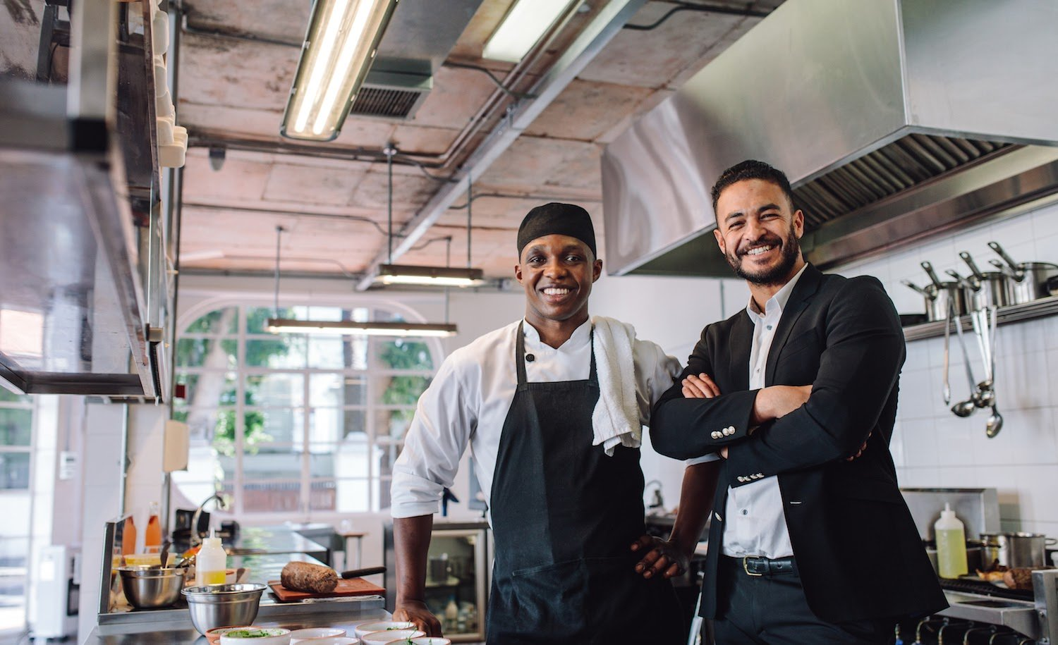 Restaurant mission statement: A business man and a cook stand in a restaurant kitchen