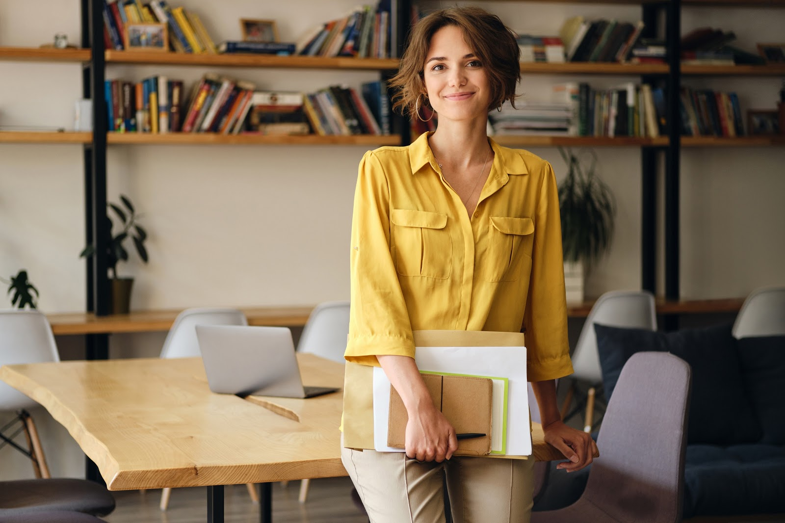 How to become a restaurant manager: Woman holds documents and smiles at camera