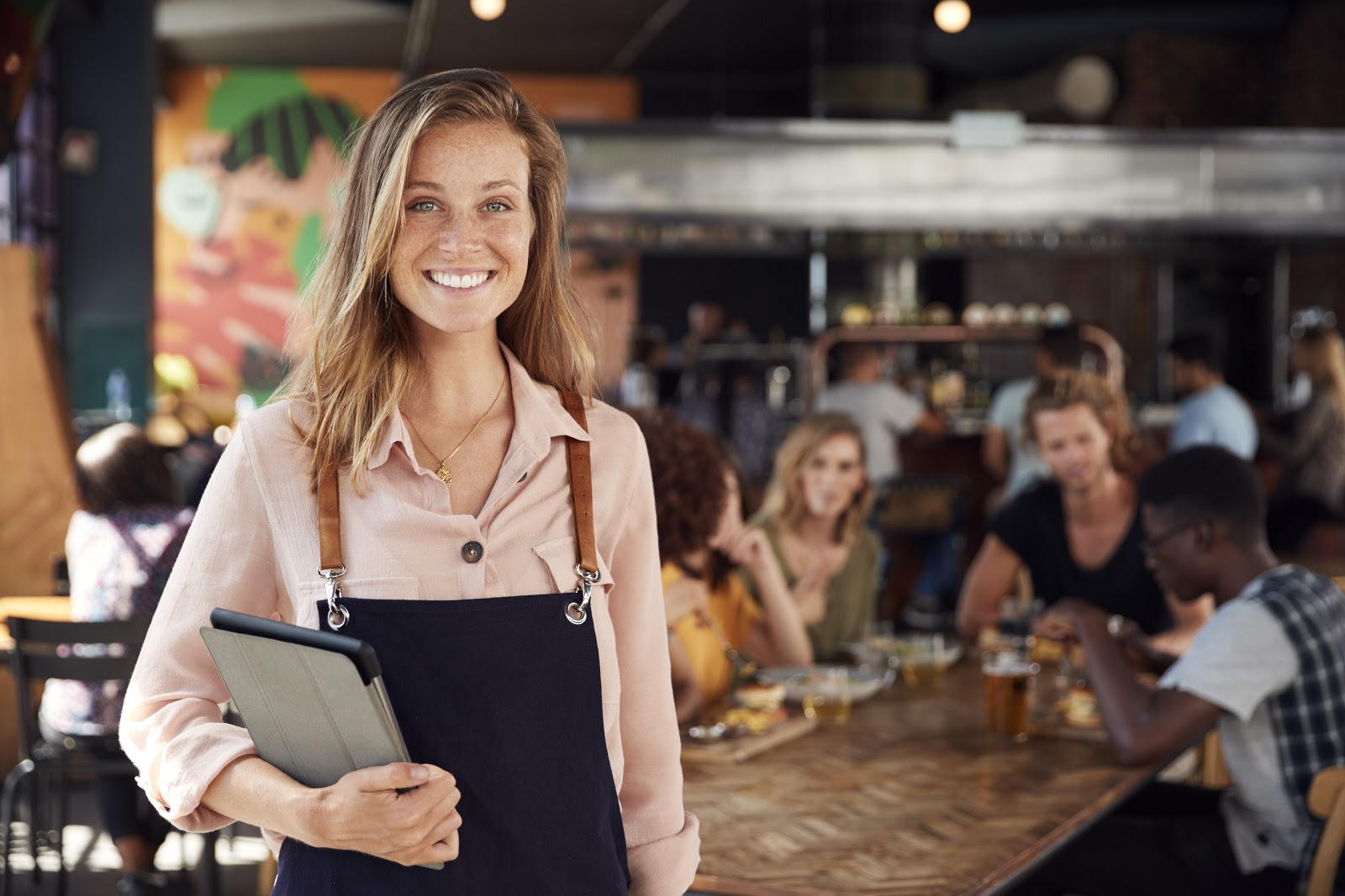Server stands in restaurant holding iPad smiling at camera