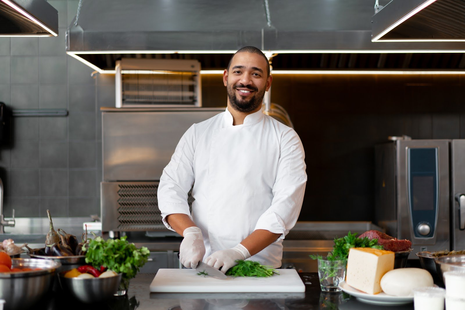 Internal promotion: Chef smiles at camera while chopping lettuce