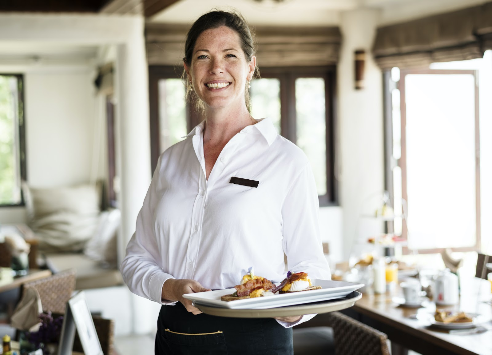 Internal promotion: Server smiles at camera while holding tray of food