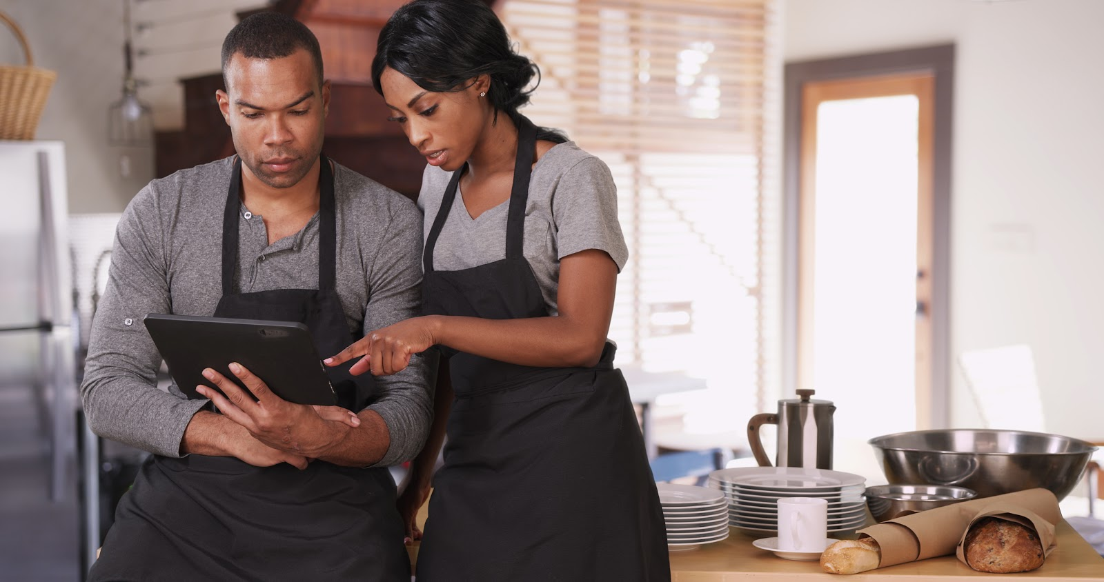 How to become a restaurant manager: Two servers look at tablet together