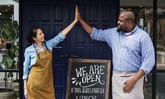 "Restaurant mission statement: Two restaurant owners high-five in front of a ""We are open"" sign"