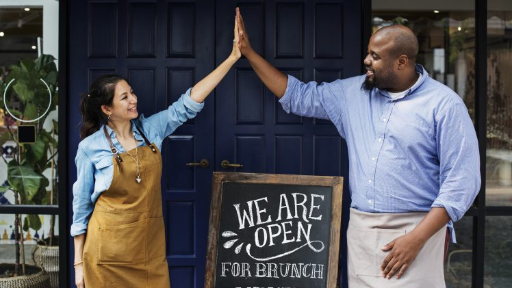 """Restaurant mission statement: Two restaurant owners high-five in front of a """"We are open"""" sign"""
