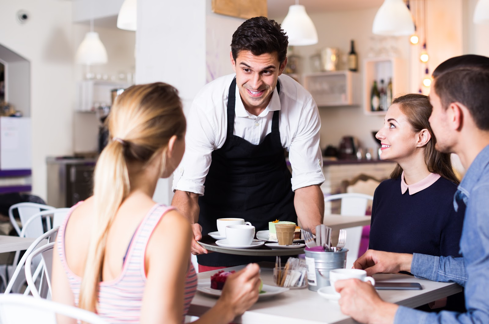 Server holds tray of coffee drinks next to table of guests