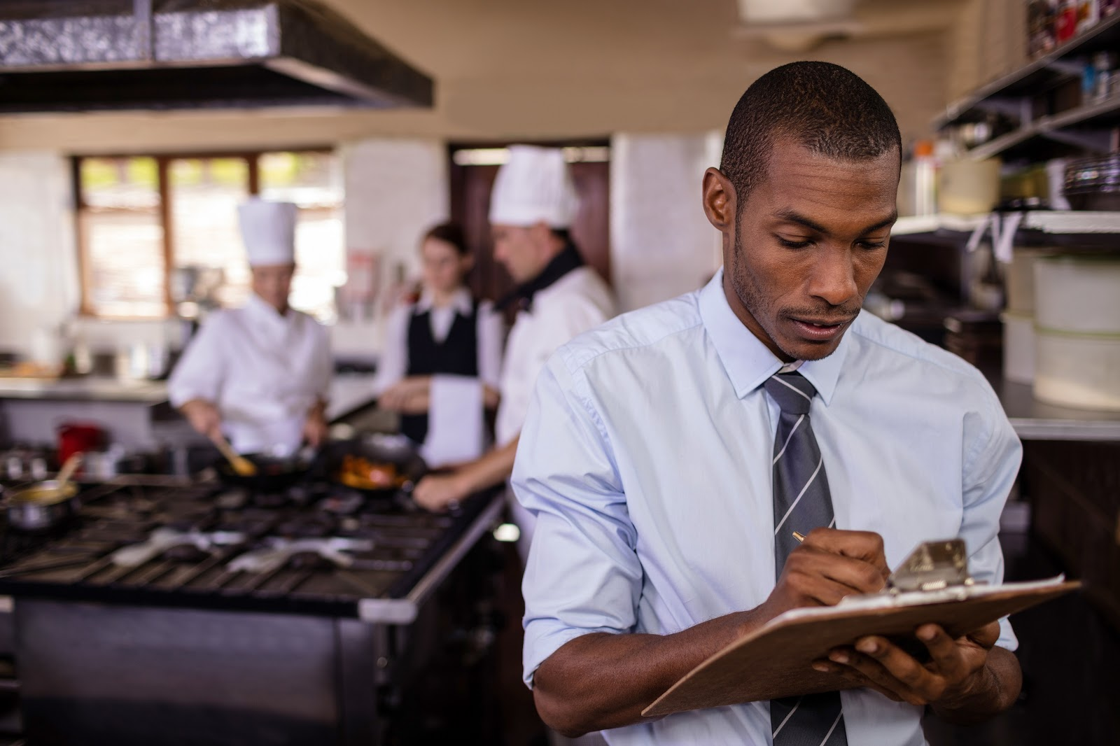 Man takes notes on clipboard with kitchen staff in background