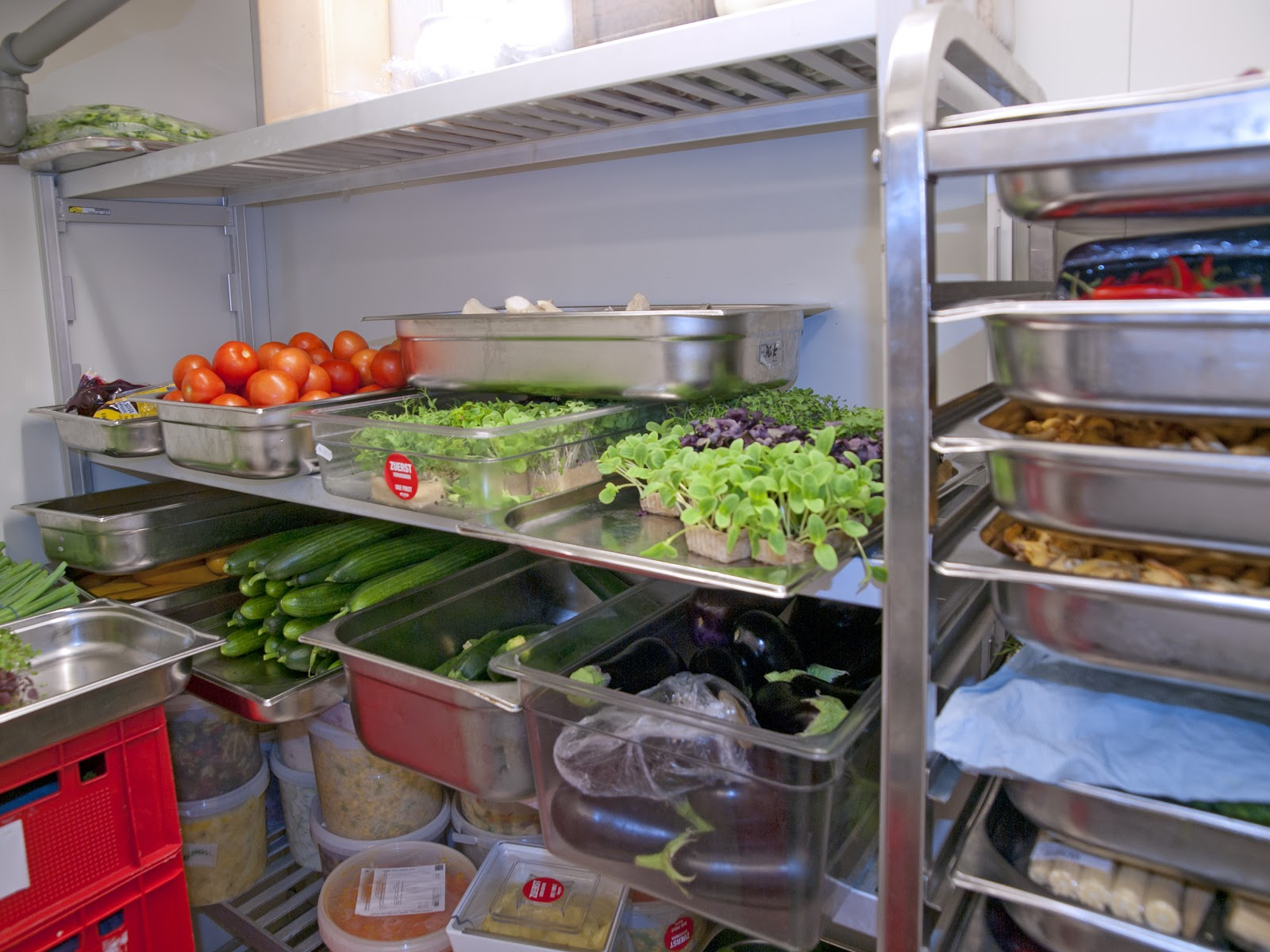 Health code violations: Veggies and trays of food in a commercial fridge