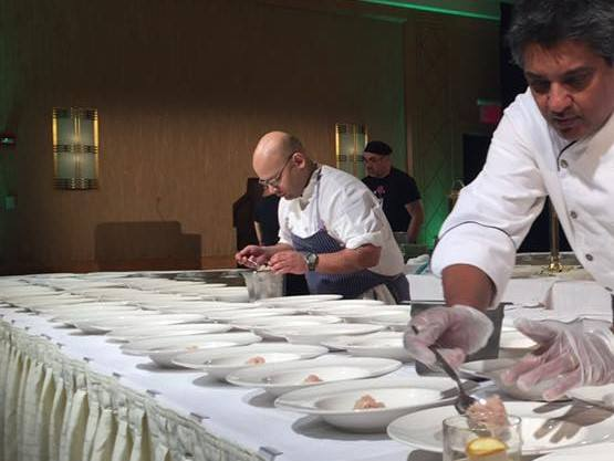 Zia preparing plates of food with a colleague.