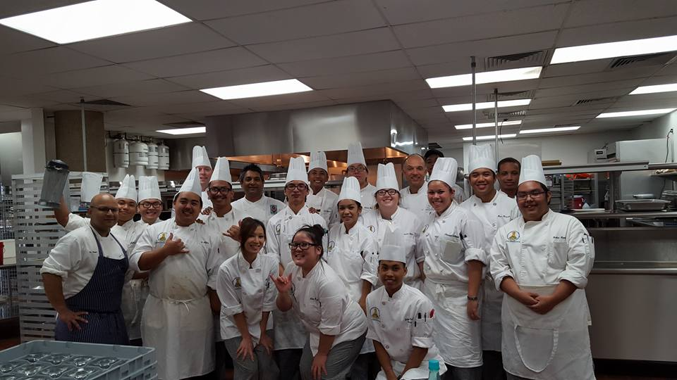 Zia (far left) posing proudly with his kitchen staff.
